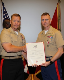 Maj. Travis S. Bowser, right, operations officer, Physical Inventory Control Division, G4, MARCORLOGCOM, receives the Meritorious Service Medal from Maj.Gen. Joseph F. Shrader, commanding general, MARCORLOGCOM, during a ceremony held at Base Theatre aboard MARCORLOGBASES Albany, GA., May 30. Bowser served 24 years in the Marine Corps.