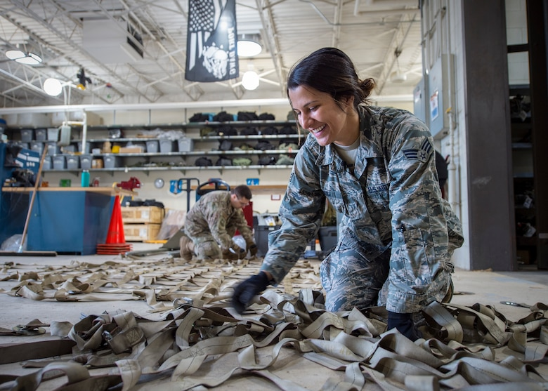 U.S. Air Force Senior Airman Marissa Ricci, from the 133rd Small Air Terminal, lays out cargo straps to secure palletized boxes of food in St. Paul, May 18, 2019.