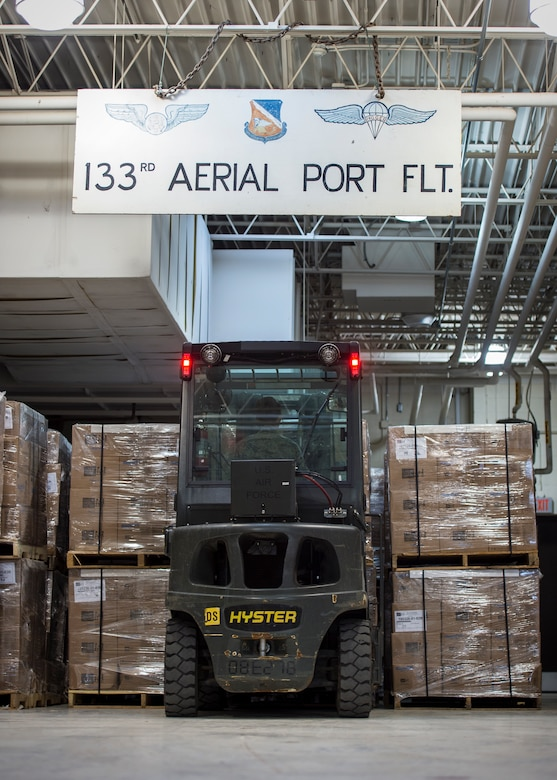 U.S. Air Force Airmen from with the 133rd Small Air Terminal load boxes of food onto pallets in St. Paul, May 18, 2019.