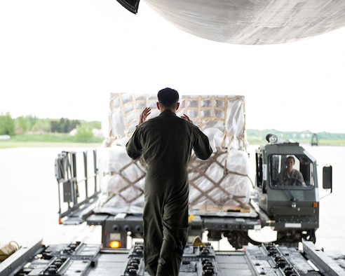 A loadmaster from the 312th Airlift Squadron guides an Airman from the 133rd Small Air Terminal to the C-5 Galaxy in St. Paul, Minn., May 22, 2019.