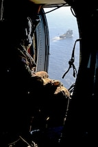An Army Soldier observes a helicopter preparing to land on a ship.