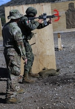 A U.S. Army Soldier coaches a member of the Mexican Marines during weapons training