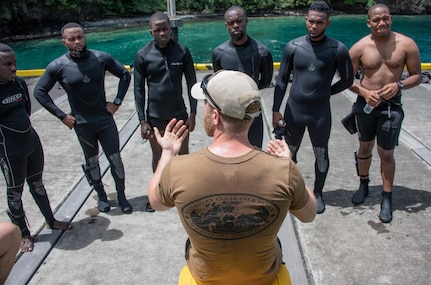 A Canadian Forces Clearance Diver delivers a post-dive brief with divers from St. Vincent and the Grenadines, Mexico, Bahamas and Trinidad and Tobago