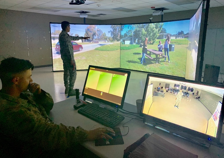 Airman 1st Class Valric Suyom, a recent graduate of the Security Forces apprentice course, participates in a use of force training scenario in the Multiple Interactive Learning Objectives, or MILO, simulator as Staff Sgt. James McKinney, 343rd Training Squadron instructor, guides the training at Joint Base San Antonio-Lackland May 29. The MILO system puts student in various interactive use of force training scenarios, including the potential application of deadly force, through the use of enhanced video screens.