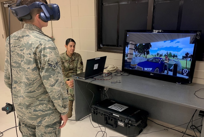 Airman 1st Class Taylor Waldron, a recent graduate of the Security Forces apprentice course, participates in a use of force training scenario in virtual reality environment simulator as Staff Sgt. Marcia Maldonado, 343rd Training Squadron instructor, facilitates training at Joint Base San Antonio-Lackland May 29. The 343rd Training Squadron has added the VR training simulators as part of a beta-test in conjunction with a civilian vendor at no cost to the unit through a partnership with AFWERX.