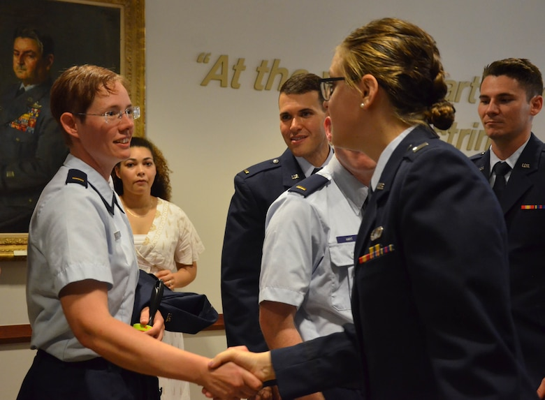 2nd Lt. Cynthia A. Schroll (left) shakes hands with her Officer Training School instructor, 1st Lt. Claire M. Krokker, after Schroll's commissioning ceremony May 30, 2019, as members of her flight look on.  (U.S. Air Force photo by Susan A. Romano)