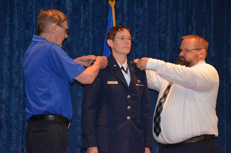 2nd Lt. Cynthia A. Schroll (center) stands at attention as her father Stephen (left) and brother Brandon (right) pin on her second lieutenant bars after she took the oath of commissioning at Officer Training School May 30, 2019.  (U.S. Air Force photo by Susan A. Romano)