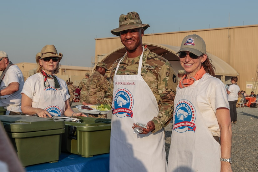 More than 40 volunteers from Minnesota flew halfway around the world to serve a steak dinner to Soldiers of the 34th Red Bull Infantry Division deployed to Camp Arifjan in Kuwait this evening. At the same time, the Twin Cities-based Serving Our Troops organization is serving a steak dinner to family members and friends of the Soldiers back home at the Saint Paul RiverCentre. As Soldiers and their families enjoy steaks donated by a number of Twin Cities restaurants, a live-video feed has connected the two sites, giving troops and their loved ones the opportunity to enjoy dinner together. During this evening's event, Serving Our Troops, which has been supporting military members and their families for 15 years, served its 100,000th steak.