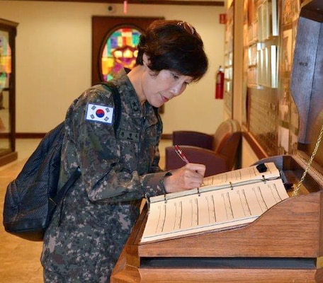 Republic of Korea Army Brig. Gen. Myoung-ok Kwon, superintendent for the Korea Armed Forces Nursing Academy signs the distinguished visitor log book at the U.S. Army Medical Department Center & School, Health Readiness Center of Excellence's International Military Student Office 22 years after she graduated from what is now the Captains Career Course at the HRCoE at Joint Base San Antonio-Fort Sam Houston.