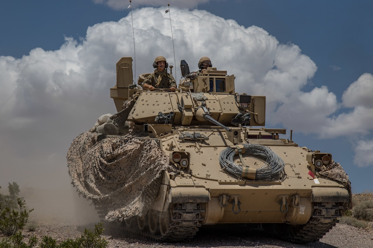 Two soldiers ride in a Bradley vehicle with a backdrop of  clouds.