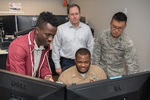 Standing, from left, Kofi Forson, product manager, James Dentice, system engineer, and Capt. Traeyoung Lee, program manager, all from Program Executive Office Digital, work with Master Chief Kristopher Boyd, an information systems technician and spectrum manager with the USS Nimitz Carrier Strike Group 11, at the Hanscom Collaboration and Innovation Center, Hanscom Air Force Base, Mass., May 16, 2019. Sailors from the Nimitz worked with Digital at the Hanscom Collaboration and Innovation Center to test options for this a single hub for intelligence, surveillance and reconnaissance between separate Distributed Common Ground Systems. (U.S. Air Force photo by Jerry Saslav)