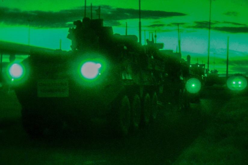 Military vehicles wait in line with their lights shining in a greenish twilight.