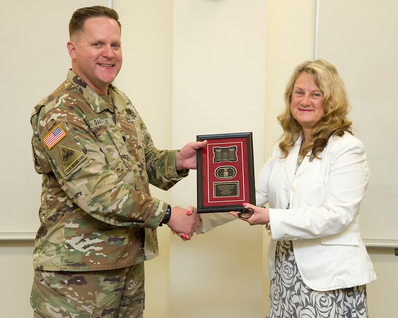 Lt. Col. Hugh Darville, Huntsville Center commander, presents Sandi Zebrowski with a token of appreciation during a retirement ceremony at Huntsville Center in May. Zebrowski served as the director of the Center's Environmental and Munitions Center of Expertise since 2008.