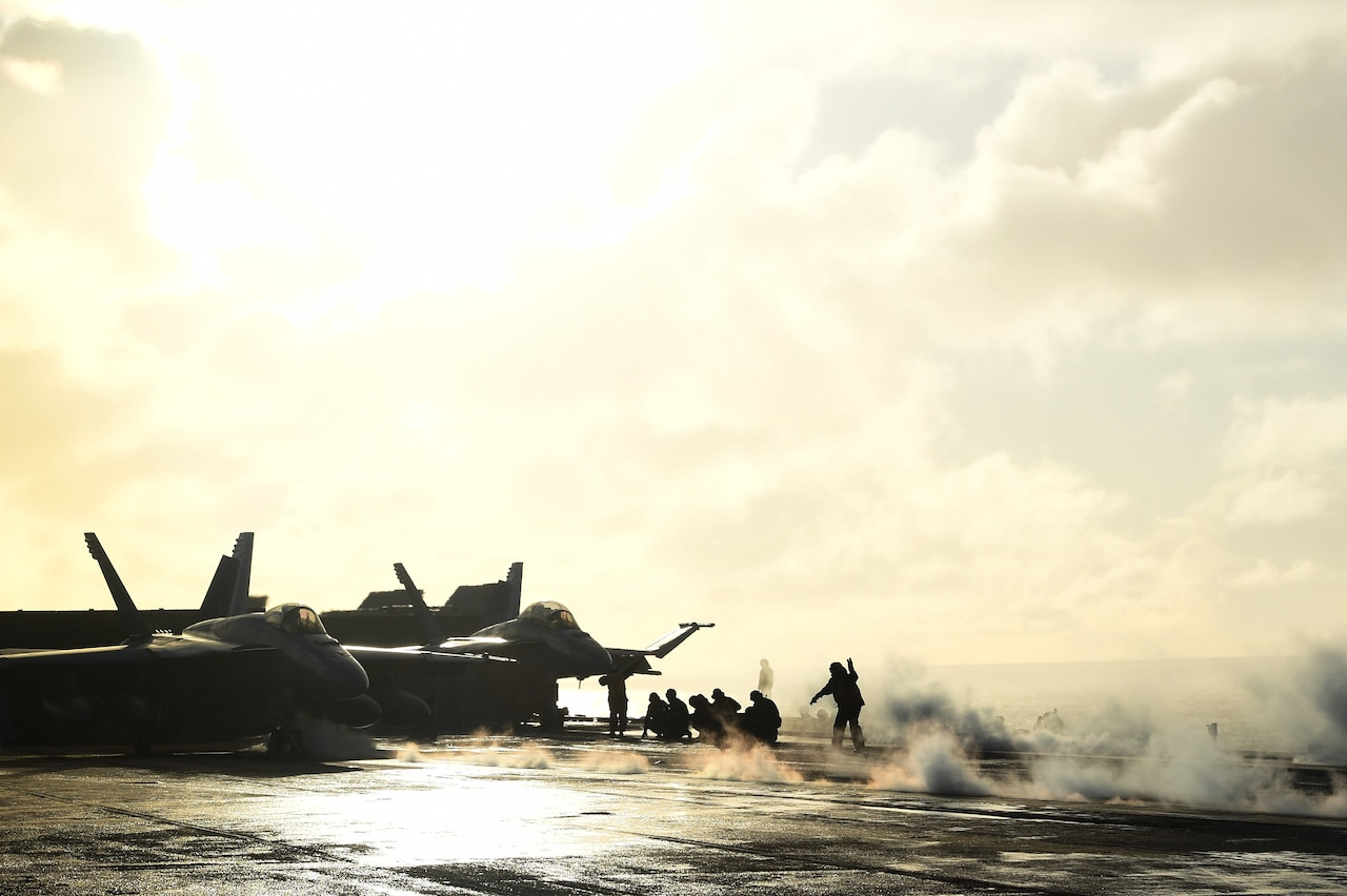 Steam surrounds jets on a carrier deck.