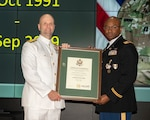 A Navy and Army officer stand on stage holding framed certificate