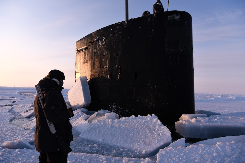 A submarine conning tower sticks through Arctic ice.