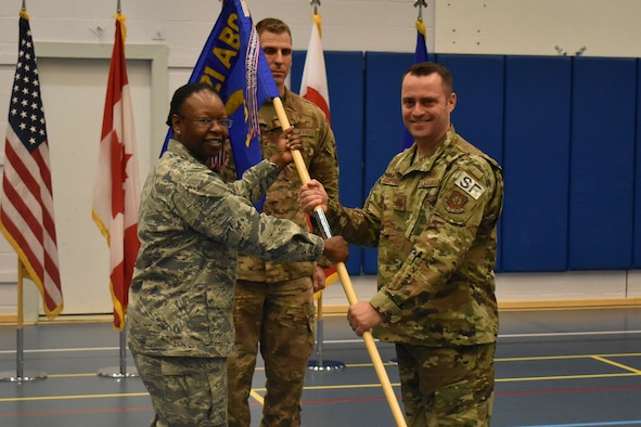 THULE AIR BASE, Greenland – Capt. Glenn Bowersox, 821st Security Forces commander, receives the guidon from Col. Mafwa Kuvibidila, 821st Air Base Group commander during a change of command ceremony, May 30, 2019. The 821st SFS is responsible for security of the 254 square-mile Thule defense area. This area includes a Ballistic Missile Early Warning System, satellite control and tracking facilities, transient aircraft, and the Air Force's only deep sea port. (Courtesy photo)