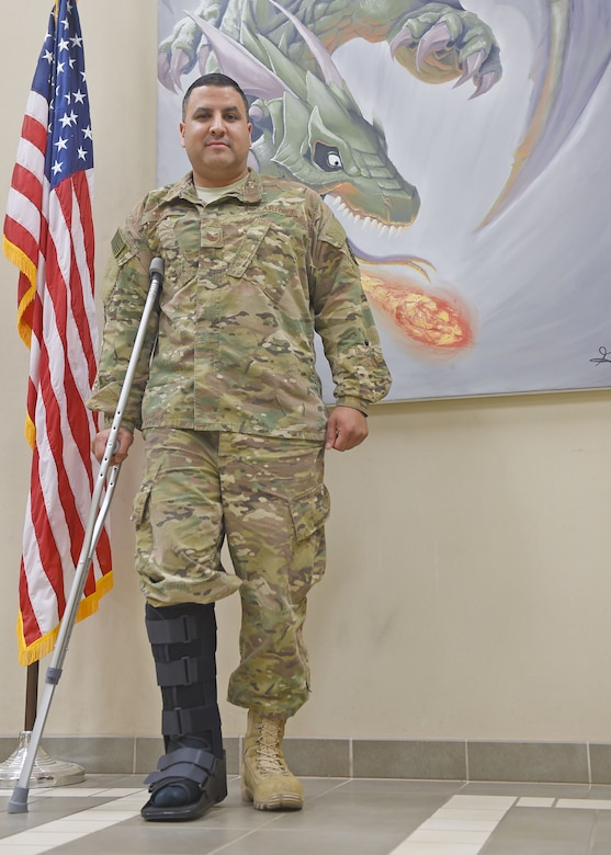 An Airman with a cast on his foot poses for a photo in front of an American flag