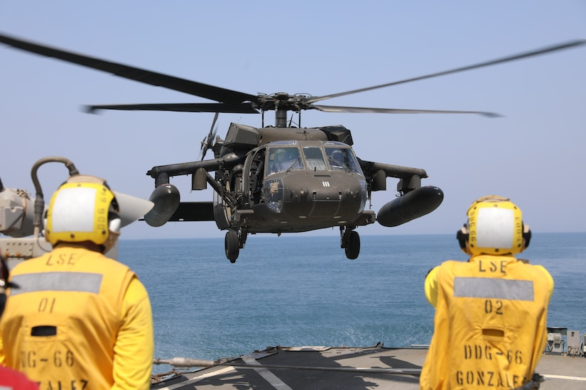 A U.S. Navy Sailor guides a U.S. Army UH-60 Black Hawk helicopter assigned to Bravo Company, 2nd Battalion, 147th Aviation Regiment, 8th Battalion, 229th Aviation Regiment during deck landing qualifications aboard the Arleigh Burke-class guided-missile destroyer USS Gonzalez (DDG 66), May 22, 2019 in the Arabian Gulf. The Gonzalez deployed to the U.S. Central Command area of operations to strengthen security and stability of the region. Deck landing qualifications increase interoperability between U.S Army and Navy personnel.