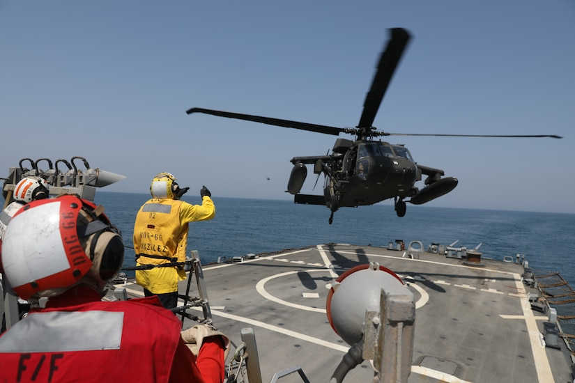 A U.S. Navy Sailor guides a U.S. Army UH-60 Black Hawk helicopter assigned to Bravo Company, 2nd Battalion, 147th Aviation Regiment, currently attached to 8th Battalion, 229th Assault Helicopter Battalion, in for a deck landing qualification aboard the Arleigh Burke-class guided-missile destroyer USS Gonzalez (DDG 66), May 22, 2019 in the Arabian Gulf. The Gonzalez deployed to the U.S. Central Command area of operations to strengthen security and stability of the region. The deck landing qualifications were held to increase interoperability between U.S Army and Navy personnel.