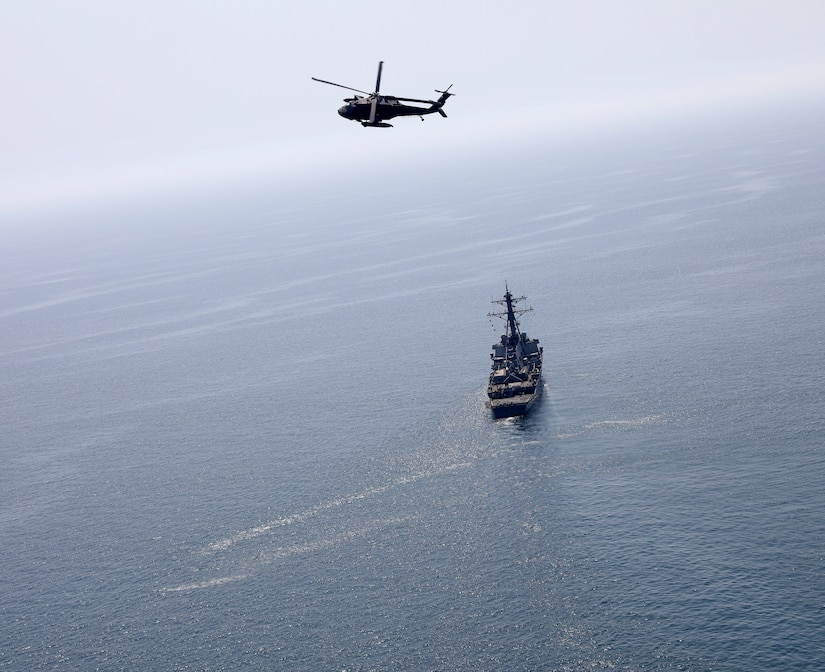A U.S. Army UH-60 Black Hawk helicopter, assigned to Bravo Company, 2nd Battalion, 147th Aviation Regiment currently attached to 8th Battalion, 229th Assault Helicopter Battalion, flies over the Arleigh Burke-class guided-missile destroyer USS Gonzalez (DDG 66), May 22, 2019 in the Arabian Gulf. The Gonzales is deployed to the U.S. Central Command area of responsibility to help provide security and stability in the region.