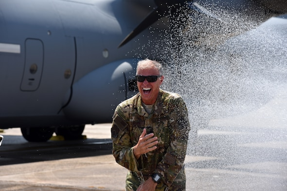 """Lt. Col. Keith Gibson, 403rd Operations Group deputy commander, is soaked with water by his family after completing his final flight June 4, 2019 at Keesler Air Force Base, Miss. Gibson's """"fini flight"""" was with the 815th Airlift Squadron aka """"Flying Jennies."""" (U.S. Air Force photo by Tech. Sgt. Christopher Carranza)"""