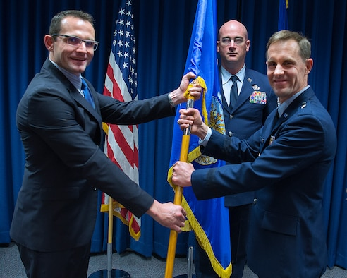 Dr. Will Roper, U.S. Air Force Assistant Secretary for Acquisition, Technology and Logistics, presents Brig. Gen. John P. Newberry with a guidon, May 31, 2019 as Newberry assumes leadership of the directorate during a ceremony at Wright-Patterson Air Force Base Ohio. Senior Master Sgt. Shawn R. Akers, Tanker Directorate superintendent stands by to take the guidon from Newberry. (U.S. Air Force photo by R.J. Oriez)
