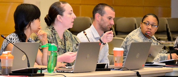 Navy Lt. Cmdr. Kyleigh Hupfl, a DLA Troop Support Medical supply chain pharmacist, middle left, speaks during a hurricane exercise at DLA Troop Support May 28, 2019 in Philadelphia.