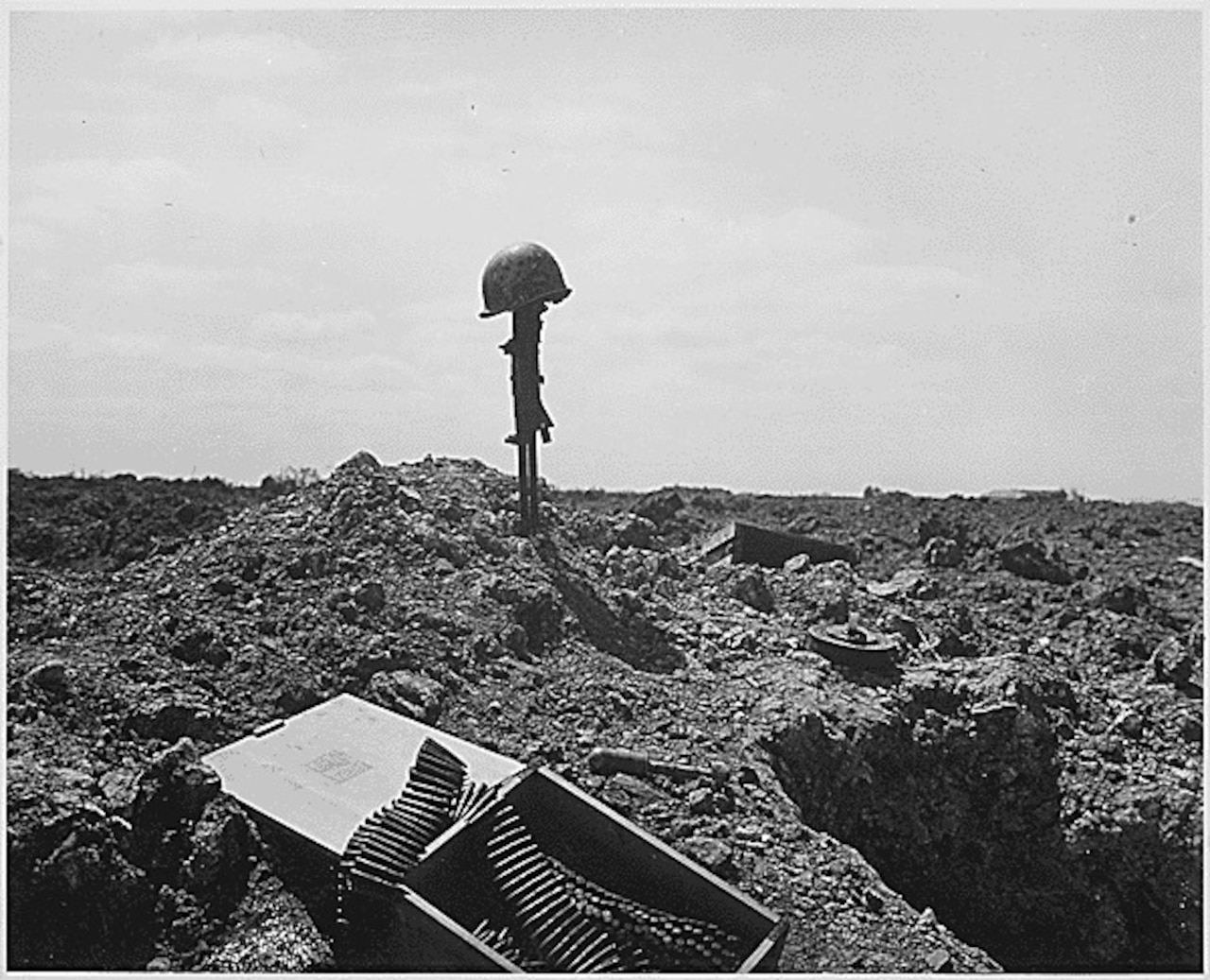 A soldier's rifle sticks straight up in the sand on a beach with a helmet on it. A box of ammo sits in the foreground.