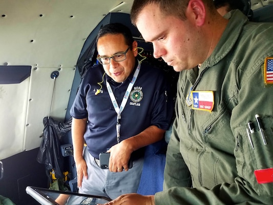 Tech. Sgt. Eric Ganley (right), 68th Airlift Squadron flight engineer, uses an electronic tablet to show Josue Tapia, Bexar County Sheriff's Office chaplain, their location in-flight on a C-5M Super Galaxy during the 433rd Airlift Wing's annual Clergy Day flight June 1 at Joint Base San Antonio-Lackland. The wing welcomed 20 ministers nominated by their Reserve Citizen Airman to get a glimpse of a unit training assembly.