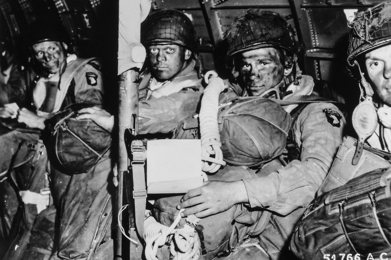 Four paratroopers in face paint sit holding their parachutes in a plane as they prepare to jump on D-Day. One of them holds a note that is his orders from Army Gen. Dwight D. Eisenhower.