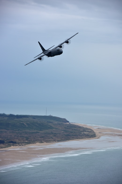 One C-130s fly in the air