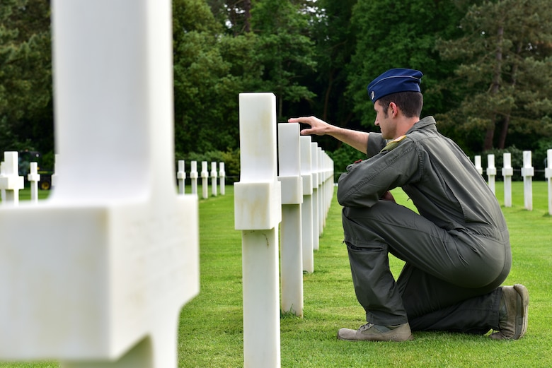 An Airman kneels at a grave site
