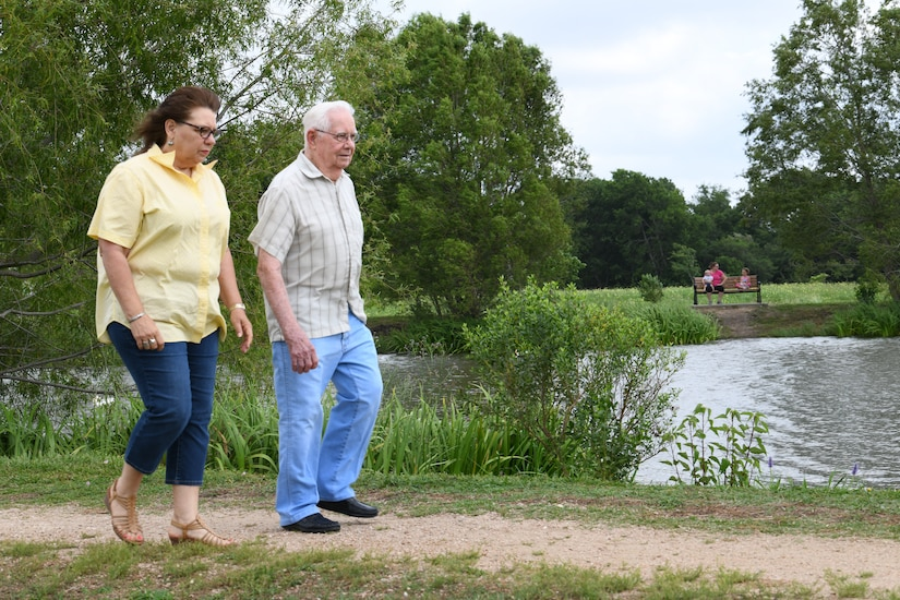A World War II vet and his daughter take a stroll by a park lake.