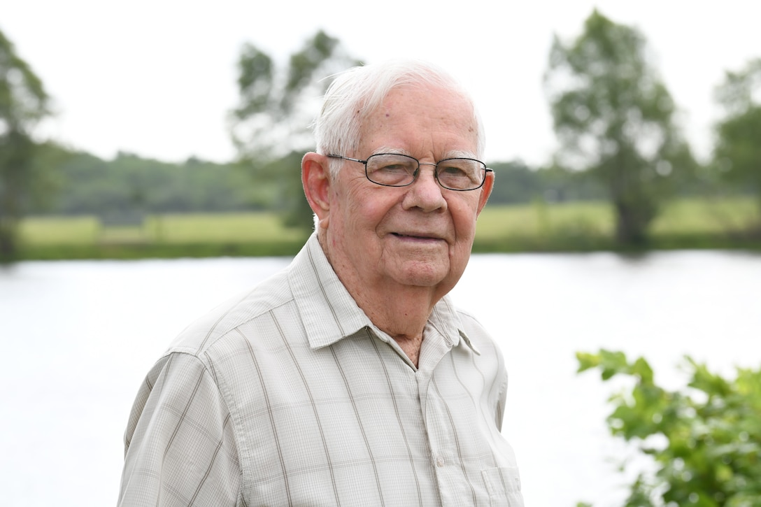 A World War II veteran wearing glasses stands in front of a lake.
