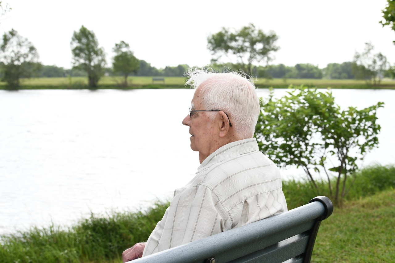 A World War II veteran sits on a bench by a lake.