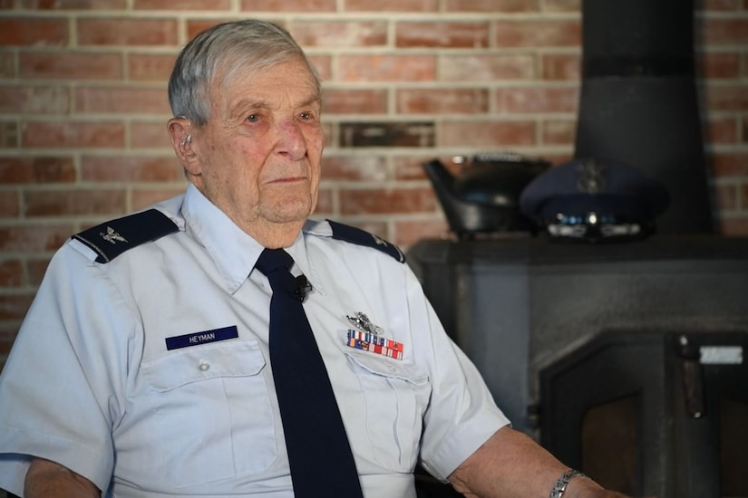 A World War II vet wearing a dress uniform sits by a fireplace.