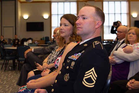 Sgt. 1st Class Greg Waters, his wife and family listen as Maj. Gen. Frank Muth delivers the opening remarks for the ceremony.