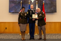 U.S. Army Recruiting Command Team, Maj. Gen Frank Muth and Command Sgt. Maj. Tabitha Gavia present Sgt. 1st Class Greg Waters with the Distinguished Service Cross.