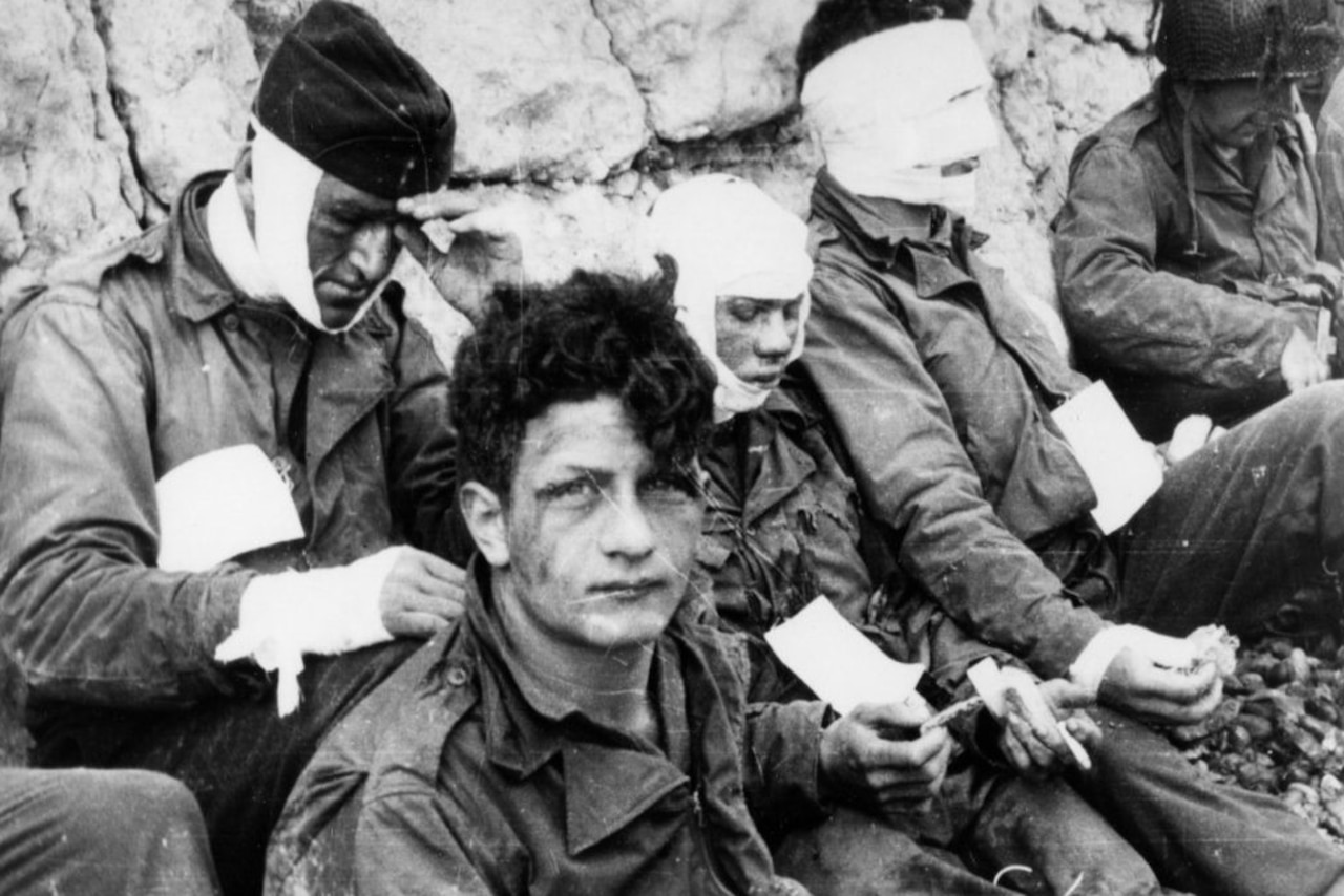 Soldiers wearing bandages sit against cliffs.