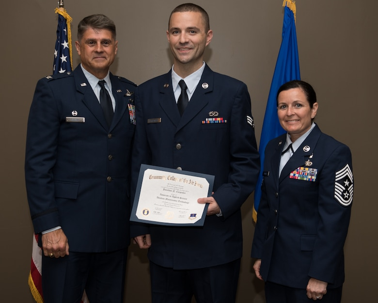 Senior Airmen Jonathon Carpenter, with the 932nd Airlift Wing, receives his Community College of the Air Force associate degree in applied science certificate from 932nd AW commander, Col. Glenn Collins during a CCAF graduation ceremony, June 2, 2019, Scott Air Force Base, Illinois. Wing leadership and fellow Airmen joined the graduates to celebrate their higher education accomplishment. (U.S. Air Force photo by Master Sgt. Christopher Parr)