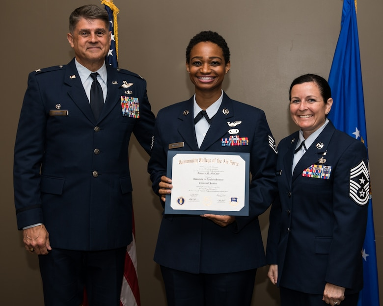 Staff Sgt. Amber McCray, with the 932nd Airlift Wing, receives her Community College of the Air Force associate degree in applied science certificate from 932nd AW commander, Col. Glenn Collins during a CCAF graduation ceremony, June 2, 2019, Scott Air Force Base, Illinois. Wing leadership and fellow Airmen joined the graduates to celebrate their higher education accomplishment. (U.S. Air Force photo by Master Sgt. Christopher Parr)