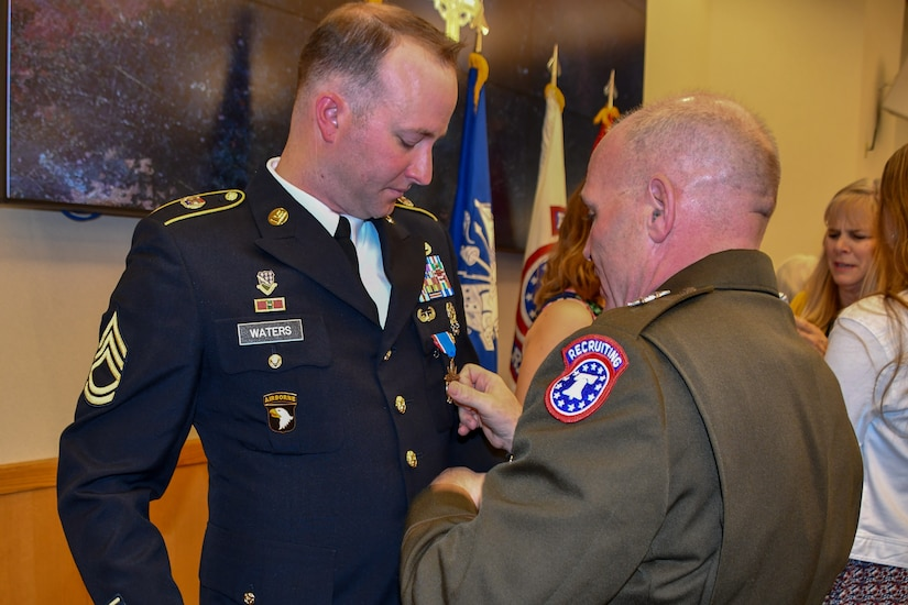 Maj. Gen. Frank Muth adjusts Sgt. 1st Class Greg  Waters newly pinned Distinguished Service Cross medal.