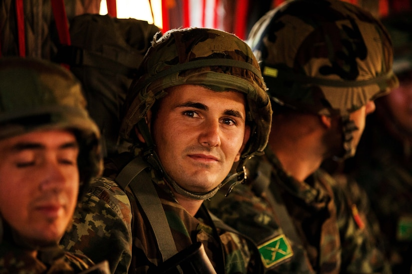 Military personnel in camouflage uniforms and combat helmets sit side by side in a helicopter.