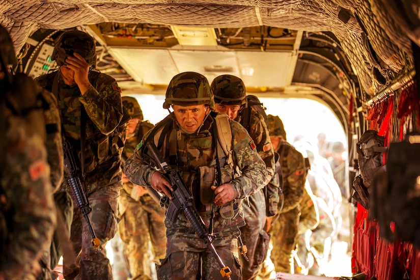 Military personnel carrying rifles enter the back of a helicopter.