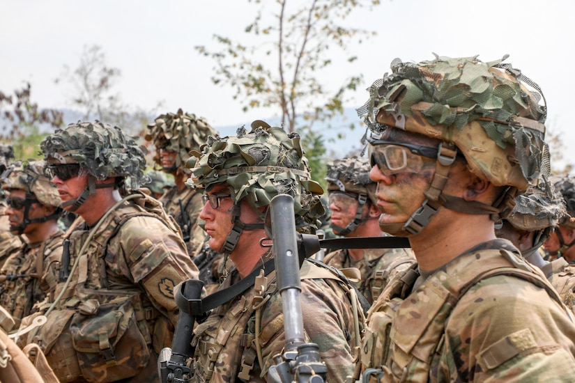 Military personnel in camouflage uniforms stand outdoors in formation.
