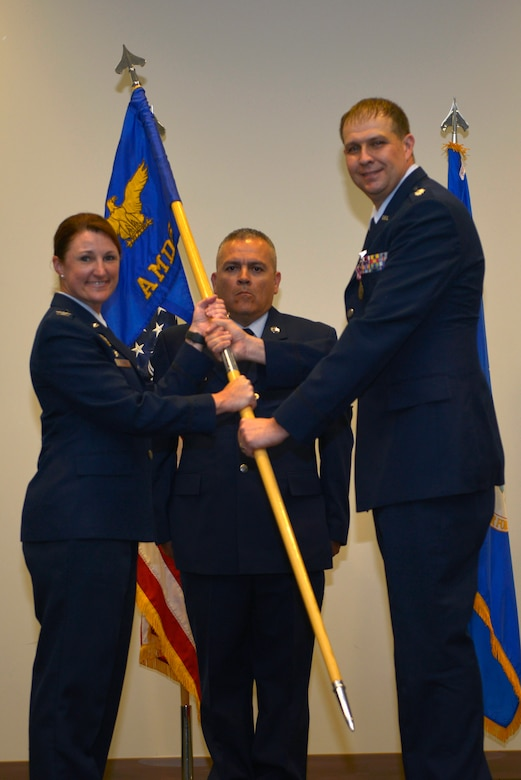 U.S. Air Force Col. Beatrice T. Dolihite, 81st Medical Group service commander, receives the 81st Aerospace Medicine Squadron guidon from Lt. Col. Michael A. Blowers, outgoing 81st AMDS commander, during the 81st AMDS change of command ceremony inside the Roberts Maintenance Facility at Keesler Air Force Base, Mississippi, June 4, 2019. The passing of the guidon is a ceremonial symbol of exchanging command from one commander to another. (U.S. Air Force photo by Airman Seth Haddix)