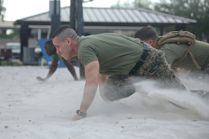 """1st Sgt. Adrian Munoz low crawls through the sand during the """"Throwdown at Fightertown"""" aboard Marine Corps Air Station Beaufort, May 31. Munoz is the company First Sergeant of Combat Logistics Company-23 aboard the air station."""