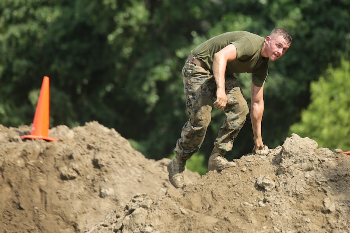 """Lance Cpl. Jacob Hiber summits and obstacle during """"Throwdown at Fightertown"""" aboard Marine Corps Air Station Beaufort, May 31. The event pitted teams of Marines against each other, testing their strength and Endurance."""