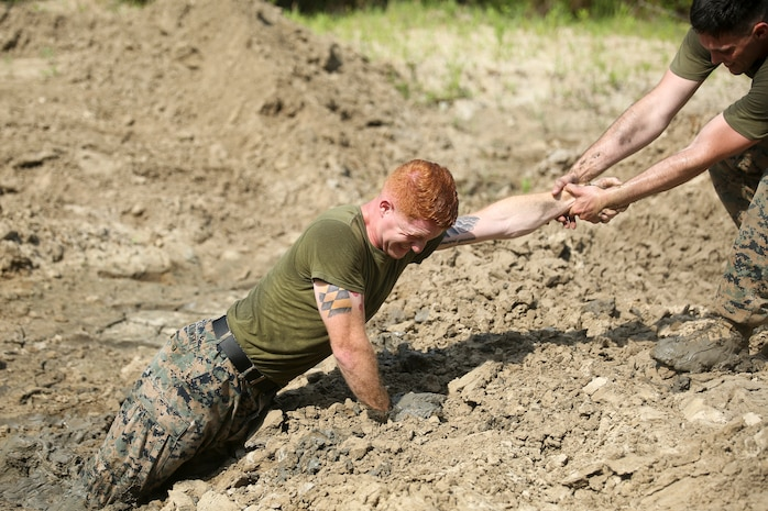 """Cpl. Cederic Graczowski gets a helping hand from Sgt. Adam Jordan during the """"Throwdown at Fightertown"""" aboard Marine Corps Air Station Beaufort, May 31. The event pitted teams of Marines against each other testing their strength and endurance."""